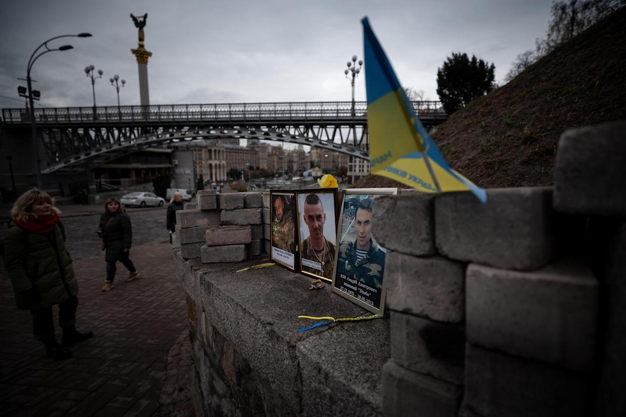 A woman looks at the photos of demonstrators who were killed during the 2014 Maidan Square protests in Kiev. (Photo: Agron Dragaj for Yahoo News)