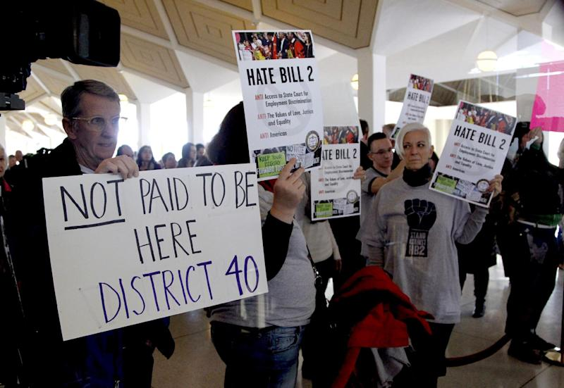 Opponents of HB2 hold signs outside the North Carolina House chambers gallery as the North Carolina General Assembly convenes for a special session at the Legislative Building in Raleigh, N.C. on Wednesday, Dec. 21, 2016. North Carolina's legislature reconvened Wednesday to decide whether enough lawmakers are willing to repeal a 9-month-old law that limited LGBT rights, including which bathrooms transgender people can use in public schools and government buildings. (Chris Seward/The News & Observer via AP)