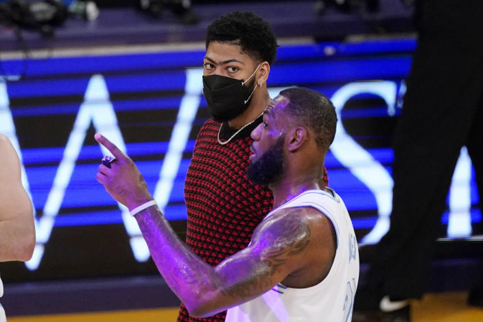 Los Angeles Lakers forward LeBron James, right, talks with Anthony Davis during the first half of an NBA basketball game against the Washington Wizards Monday, Feb. 22, 2021, in Los Angeles. (AP Photo/Mark J. Terrill)