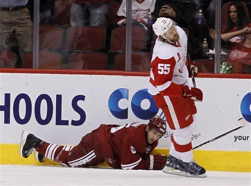 Phoenix Coyotes' Boyd Gordon, left, slides on the ice after scoring a goal as Detroit Red Wings' Niklas Kronwall (55), of Sweden, skates past during the first period in an NHL hockey game Monday, Feb. 6, 2012, in Glendale, Ariz.(AP Photo/Ross D. Franklin)