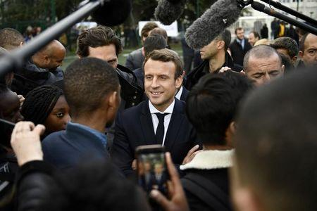Emmanuel Macron, head of the political movement En Marche !, or Onwards !, and candidate for the 2017 presidential election, speaks with youths during a campaign visit in Sarcelles