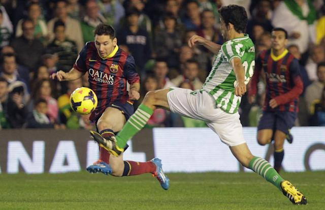 Barcelona's Lionel Messi from Argentina, left, and Betis' Antonio Caro, right, fight for the ball during their La Liga soccer match at the Benito Villamarin stadium, in Seville, Spain, Sunday, Nov. 10, 2013. (AP Photo/Angel Fernandez)