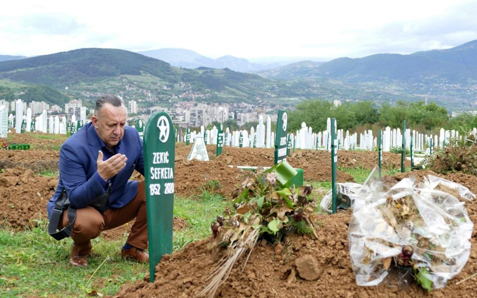 A man visits the graves of his parents in law, who died of Covid-19 complications, in Zenica, Bosnia - Almir Alic/AP