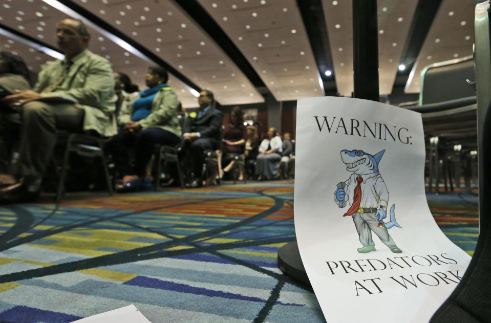 A sign warning of predatory payday lenders leans up against a chair during a speech by Consumer Financial Protection Bureau Director Richard Cordray, in Richmond, Va., Thursday, March 26, 2015.  Payday lenders would face federal rules aimed at protecting low-income borrowers from being buried by fees and debts under proposals being unveiled Thursday by the Consumer Financial Protection Bureau. (AP Photo/Steve Helber)