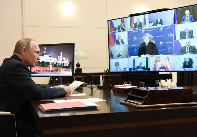 Russian President Vladimir Putin attends a meeting with members of the Security Council outside Moscow
