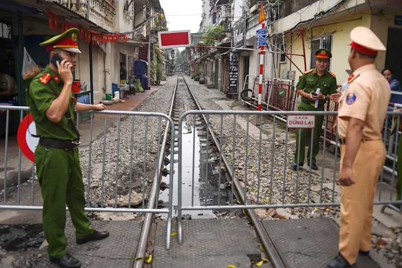 """Police personnel stand guard next to a barricade on Hanoi's popular train street on October 10, 2019 following a municipal authorities order to deal with cafes and """"ensure safety"""" on the railway track. (Photo by Nhac NGUYEN / AFP) (Photo by NHAC NGUYEN/AFP via Getty Images)"""