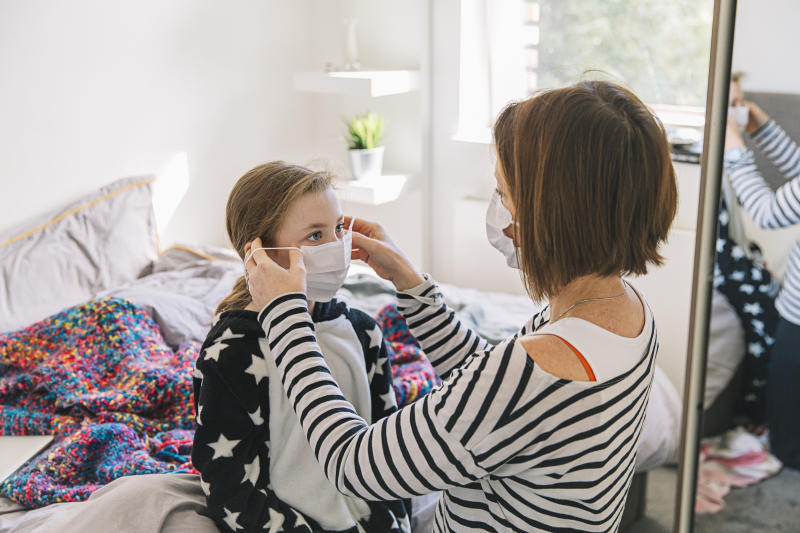 Mother putting mask on daughter