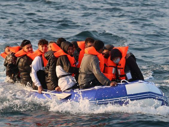 A group of migrants crossing The Channel in a small boat headed in the direction of Dover, Kent, on 10 August (PA)