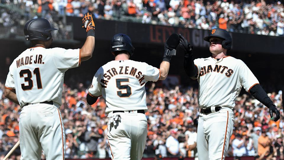 SAN FRANCISCO, CALIFORNIA - OCTOBER 03: LaMonte Wade Jr. #31, Mike Yastrzemski #5  and Logan Webb #62 of the San Francisco Giants score against the San Diego Padres in the 4th inning at Oracle Park on October 03, 2021 in San Francisco, California. (Photo by Brandon Vallance/Getty Images)