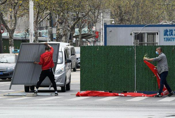 PHOTO: Workers wearing face masks remove barriers on a street in Wuhan, the epicenter of the novel coronavirus outbreak, as the city has started to loosen its lockdown, in Hubei province, China, on March 21, 2020. (China Daily/Reuters)