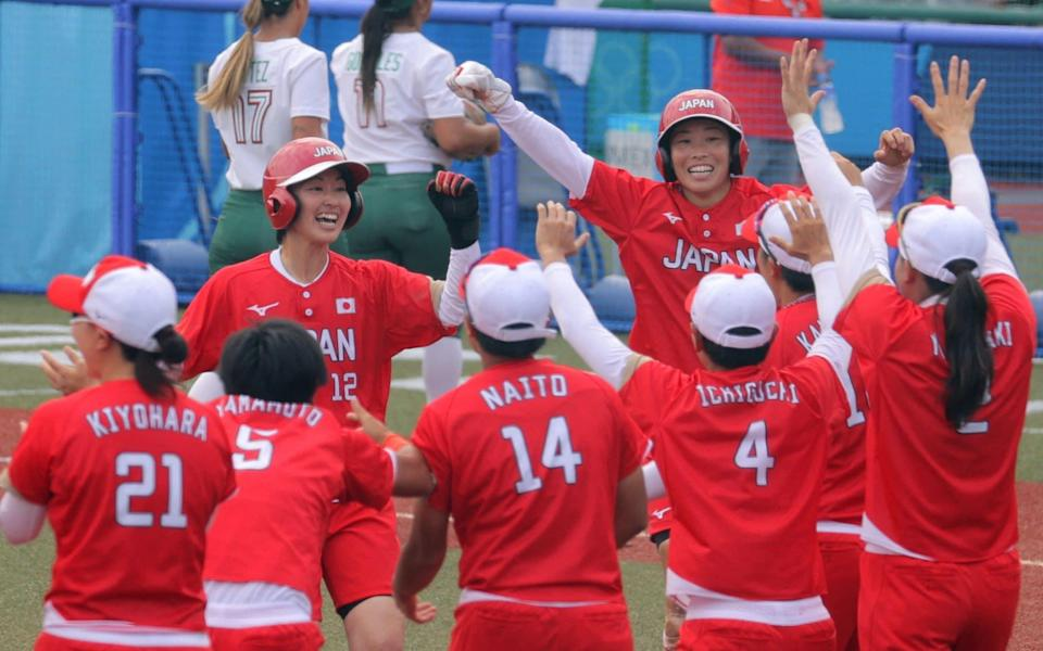 Japan's Mana Atsumi (centre L) and Eri Yamada (centre R) celebrate their victory with their teammates (front) during the Tokyo 2020 Olympic Games softball opening round game between Mexico and Japan at Fukushima Azuma Baseball Stadium in Fukushima, Japan, on July 22, 2021. - AFP