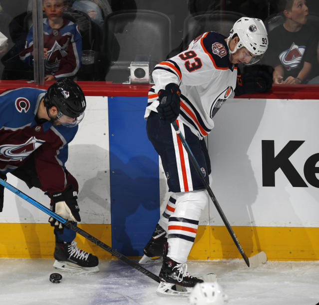 Colorado Avalanche center Derick Brassard, left, battles for control of the puck with Edmonton Oilers center Ryan Nugent-Hopkins in the first period of an NHL hockey game Tuesday, April 2, 2019, in Denver. (AP Photo/David Zalubowski)