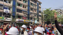 In this image from video, residents watch from their balconies as protesters flashing three-fingered salutes march past Saturday, Feb. 6, 2021, in Yangon, Myanmar. The military authorities in charge of Myanmar broadened a ban on social media following this week's coup, shutting access to Twitter and Instagram, while street protests continued to expand Saturday as people gathered again to show their opposition to the army takeover.(AP Photo)