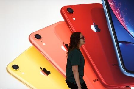 An Apple Store employee walks past an illustration of iPhones at the new Apple Carnegie Library during the grand opening and media preview in Washington