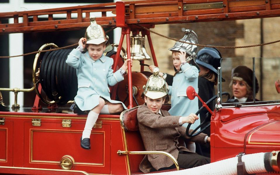 Peter, Harry and William play on a fire engine on the Sandringham Estate on January, watched by The Princess of Wales, in 1988 - Anwar Hussein