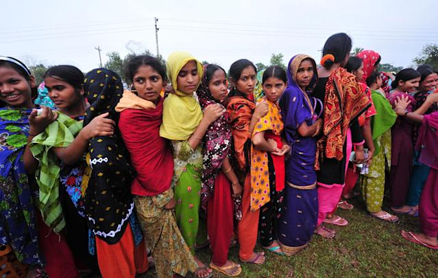 Bangladeshi garment workers employed at Rana Plaza, the garment factory building that collapsed, stand in a queue to receive wages from the Bangladesh Garment Manufacturers and Exporters Association in Savar, near Dhaka, Bangladesh, Tuesday, May 7, 2013. Hundreds of survivors of last month's collapse of a building housing garment factories in Bangladesh protested for compensation Tuesday, as the death toll from the country's worst-ever industrial disaster passed 700. (AP Photo)