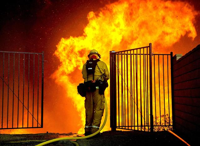 <p>A firefighter battles flames next to homes during the Holy Fire in Lake Elsinore, Calif., Aug. 9, 2018. (Photo: David McNew/EPA-EFE/REX/Shutterstock) </p>