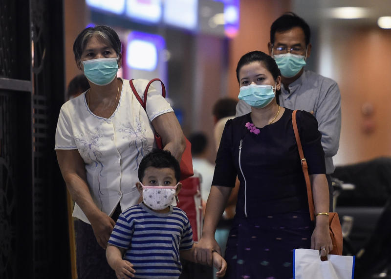 People wear protective facemasks at the Yangon international aiport in Yangon on January 31, 2020. - Myanmar airlines suspend their China flights while the World Health Organization declared a global emergency over the new coronavirus, as China reported on January 31 the death toll had climbed to 213 with nearly 10,000 infections. (Photo by Ye Aung THU / AFP) (Photo by YE AUNG THU/AFP via Getty Images)