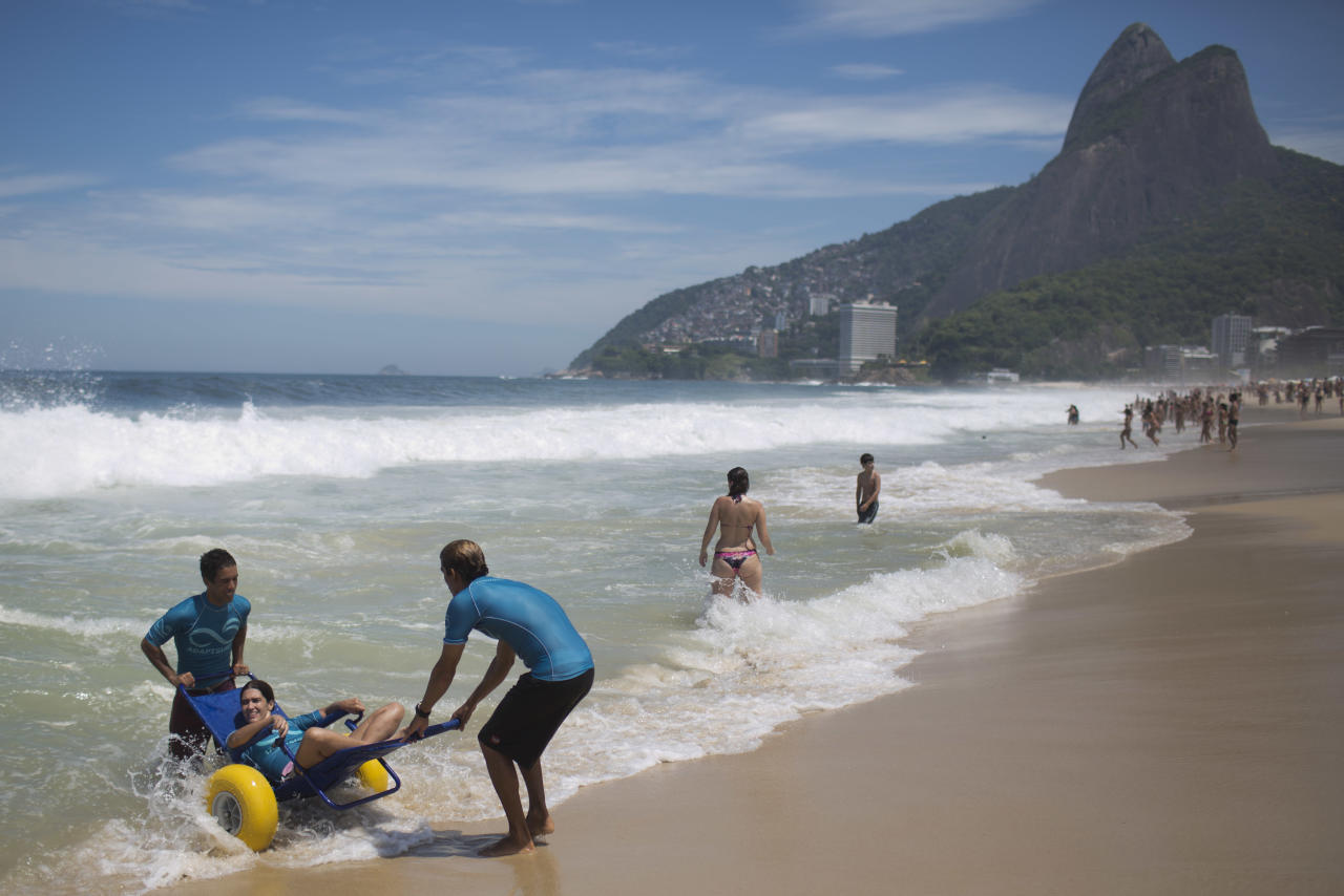 In this March 10, 2013 photo, Renata Glasner, is helped by AdaptSurf volunteers into the water at Leblon beach in Rio de Janeiro, Brazil. Glasner, who was diagnosed with multiple sclerosis four years ago, is one of dozens of disabled people on this special strip of Rio de Janeiro beach who is conquering the waves. Glasner is able to savor that experience on a weekly basis thanks to AdaptSurf, a Rio-based non-governmental organization that aims to make beaches accessible to the disabled and encourage them to practice water sports. (AP Photo/Felipe Dana)