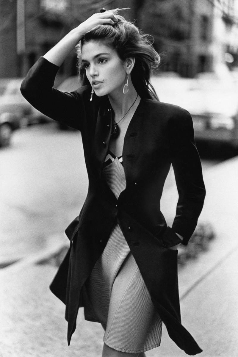 NEW YORK, NY - FEBRUARY 1: Model, Cindy Crawford, wearing a fitted black wool coat over a striped silk slip dress, by Gianni Versace, walking on a sidewalk, running her hand through her hair CREDIT MUST READ: Arthur Elgort/Conde Nast via Getty Images. (Photo by Arthur Elgort/Conde Nast via Getty Images)