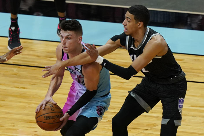 Miami Heat guard Tyler Herro (14) looks to pass the ball under pressure from Sacramento Kings guard Tyrese Haliburton (0) during the first half of an NBA basketball game, Saturday, Jan. 30, 2021, in Miami. (AP Photo/Marta Lavandier)