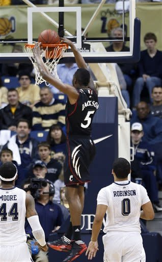 Pittsburgh's Durand Johnson (5) dunks after getting by Pittsburgh's James Robinson (0) and J.J. Moore (44) in the first half of the NCAA college basketball game, Monday, Dec. 31, 2012, in Pittsburgh. (AP Photo/Keith Srakocic)