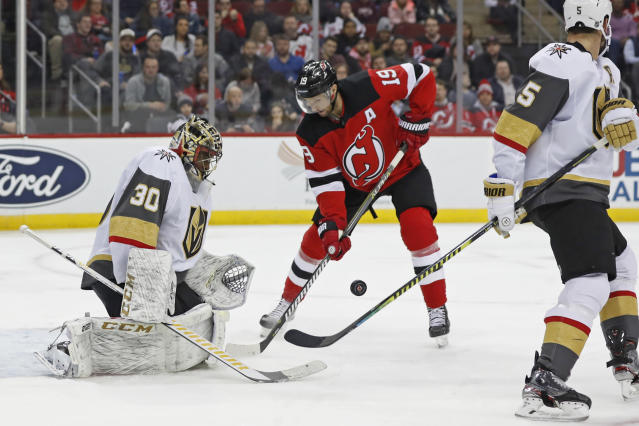 Vegas Golden Knights goaltender Malcolm Subban (30) watches the puck as it bounces in front of New Jersey Devils center Travis Zajac (19) with Golden Knights defenseman Deryk Engelland (5) watching, far right, during the second period of an NHL hockey game, Tuesday, Dec. 3, 2019, in Newark, N.J. (AP Photo/Kathy Willens)