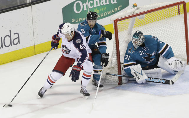 Columbus Blue Jackets' Artem Anisimov, left, is defended by San Jose Sharks' Joe Pavelski (8) as goalie Antti Niemi watches during the first period of an NHL hockey game, Friday, Feb. 7, 2014, in San Jose, Calif. (AP Photo/Marcio Jose Sanchez)
