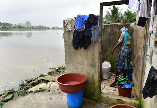 <p>Toilet cleaning in an impoverished neighborhood in Abidjan, Ivory Coast. (Photo: Issouf Sanogo/AFP/Getty Images) </p>
