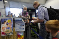 A United Airlines agent checks in passengers at the gate to board a flight to Hawaii at San Francisco International Airport in San Francisco, Thursday, Oct. 15, 2020. Coronavirus weary residents and struggling business owners in Hawaii will be watching closely as tourists begin to return to the islands on Thursday without having to self-quarantine upon arrival. (AP Photo/Jeff Chiu)