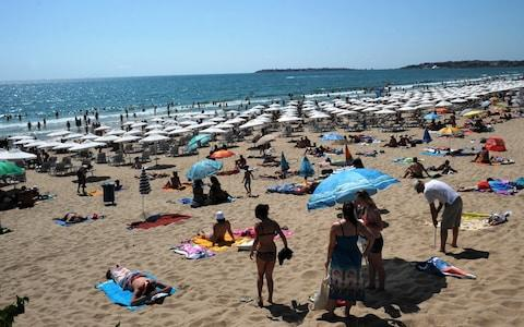 People enjoy the sun at the beach of the Black Sea resort of Sunny Beach, near the city of Bourgas - Credit: AFP/NIKOLAY DOYCHINOV