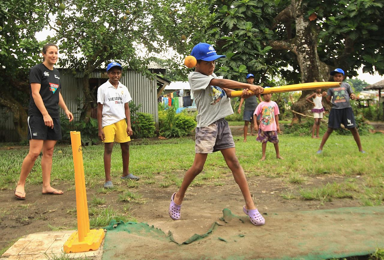 PORT VILA, VANUATU - MAY 16:  Local children play cricket with New Zealand cricketer Sara McGlashan watching during an ICC Cricket Development Program Clinic in Mele Village on May 16, 2012 in Port Vila, Vanuatu.  (Photo by Hamish Blair/Getty Images)