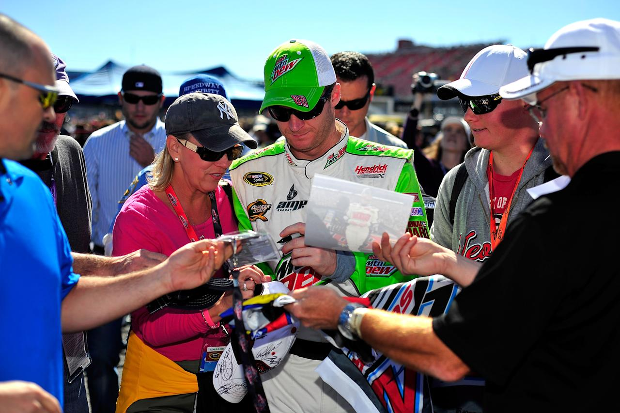 TALLADEGA, AL - OCTOBER 22:  Dale Earnhardt Jr., driver of the #88 Diet Mountain Dew Chevrolet, signs autographs during qualifying for the NASCAR Sprint Cup Series Good Sam Club 500 at Talladega Superspeedway on October 22, 2011 in Talladega, Alabama.  (Photo by Jason Smith/Getty Images)