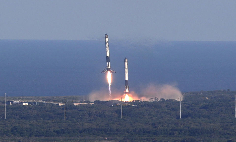 FILE - In this Thursday, April 11, 2019 file photo, SpaceX lands two of the first-stage boosters side by side, eight minutes after liftoff at the Kennedy Space Center in Cape Canaveral, Fla. (AP Photo/John Raoux)