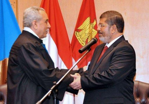 Egyptian President Mohamed Morsi (R) shakes hands with Faruq Sultan, head of the presidential election commission