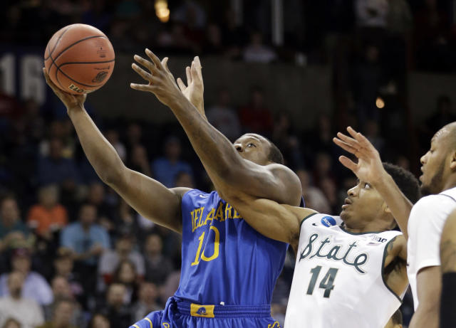 Michigan State's Gary Harris (14) tangles with Delaware's Devon Saddler during the first half in the second round of the NCAA college basketball tournament in Spokane, Wash., Thursday, March 20, 2014. (AP Photo/Elaine Thompson)