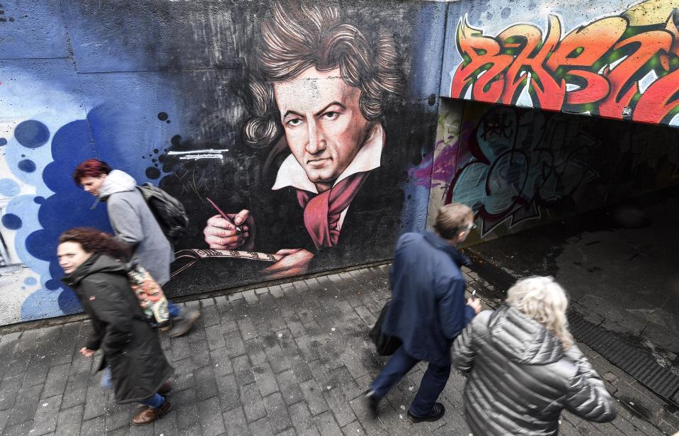 People passing a graffiti showing composer Ludwig van Beethoven on a street in Bonn, Germany, Wednesday, Feb. 19, 2020. The city of Bonn, where Beethoven was born on December 17, 1770, celebrates the 250th birthday of the great German composer with many cultural events during this year. (AP Photo/Martin Meissner)