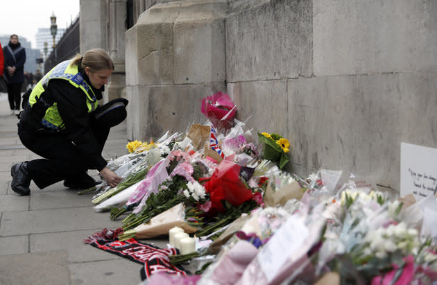 A police officer lays a floral tribute near Westminster Bridge following the attack