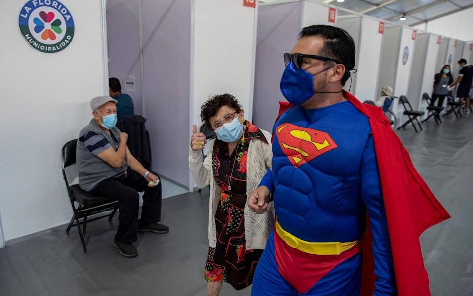 A man dressed as Superman accompanies his mother to get vaccinated in Santiago - Alberto Valdes/EPA-EFE/Shutterstock