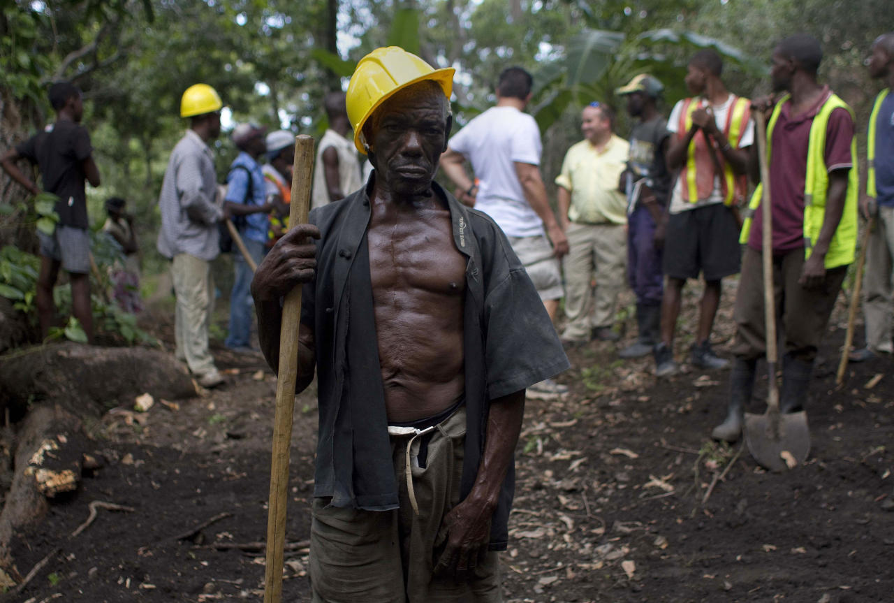 In this April 10, 2012 photo, Genove Valcimon, 70, poses for a picture as he works on a road being built through the mountains to lead to an exploratory drill site in the department of Trou Du Nord, Haiti. Haiti's land may yet hold the solution to centuries of poverty: there is gold hidden in its hills, and silver and copper too. Now, two mining companies are drilling around the clock to determine how to get those metals out, and how much it might cost. (AP Photo/Dieu Nalio Chery)