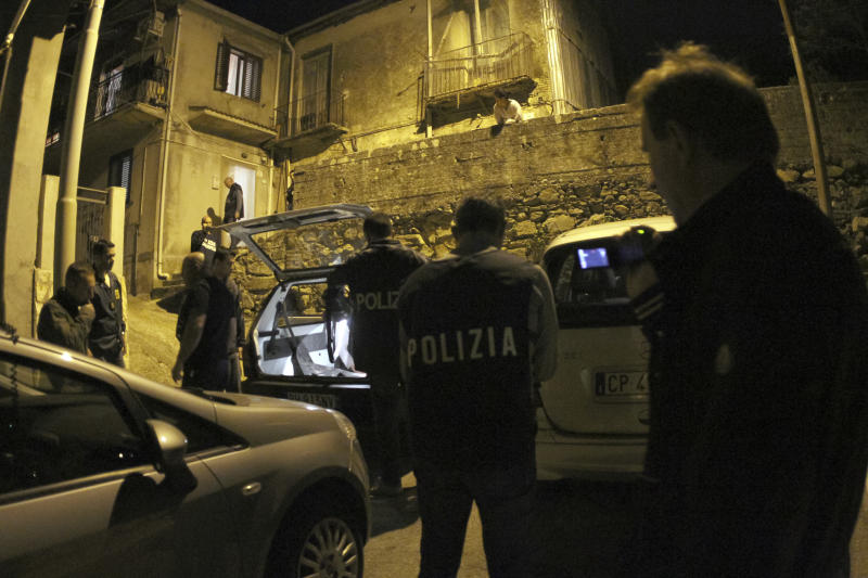Police officers stand outside a suspect's house during an operation conducted with U.S. FBI agents, in Sinopoli, southern Italy, early Thursday morning, May 7, 2015. Italian police said that in operations conducted with U.S. FBI agents they have dismantled a major drug trafficking ring whose base was a restaurant-pizzeria in New York City. At least 15 suspects have been detained by early Thursday, including three in the United States connected with the eatery in the city's Queens borough. Investigators say the crackdown further demonstrates that the 'ndrangheta, an organized crime syndicate rooted in Calabria in the toe of the Italian peninsula, have forged ever stronger ties with U.S.-based mobsters. (AP Photo/Adriana Sapone)