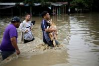 People walk througA man carries his dog as he walks with other people through a flooded street during the passage of Storm Eta, in La Lima a flooded street during the passage of Storm Eta, in La Lima