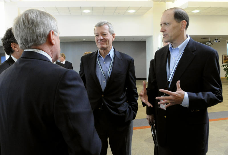 FILE - In this July 8, 2013, file photo Senate Finance Committee Chairman Sen. Max Baucus, D-Mont., left, and the House Ways and Means Committee Chairman, Rep. Dave Camp, R-Mich., talks about tax reform to 3M's Chief Technology Officer Fred Palensky left, at the 3M Innovation Center in Maplewood, Minn. Two of the most powerful members of Congress, Baucus, a Democrat, and Camp, a Republican, are touring the country to rally support for their effort to overhaul the nation's tax laws. As they work to attract other lawmakers to their cause, they've developed a close friendship and have helped Democrats and Republicans get to know each other a bit better. Their secret weapon: burgers and beer. (AP Photo/Hannah Foslien, File)