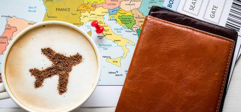 A travel airplane in a cappuccino on top of a map,tickets, and passport book.