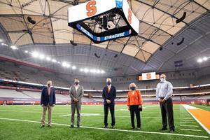 (From L to R) Syracuse University Director of Athletics John Wildhack, Syracuse City Mayor Ben Walsh, Chancellor Kent Syverud, Dr. Ruth Chen and Vice President and Chief Facilities Officer Pete Sala stand on the stadium field beneath the new roof and new center-hung video scoreboard. Courtesy: Syracuse University