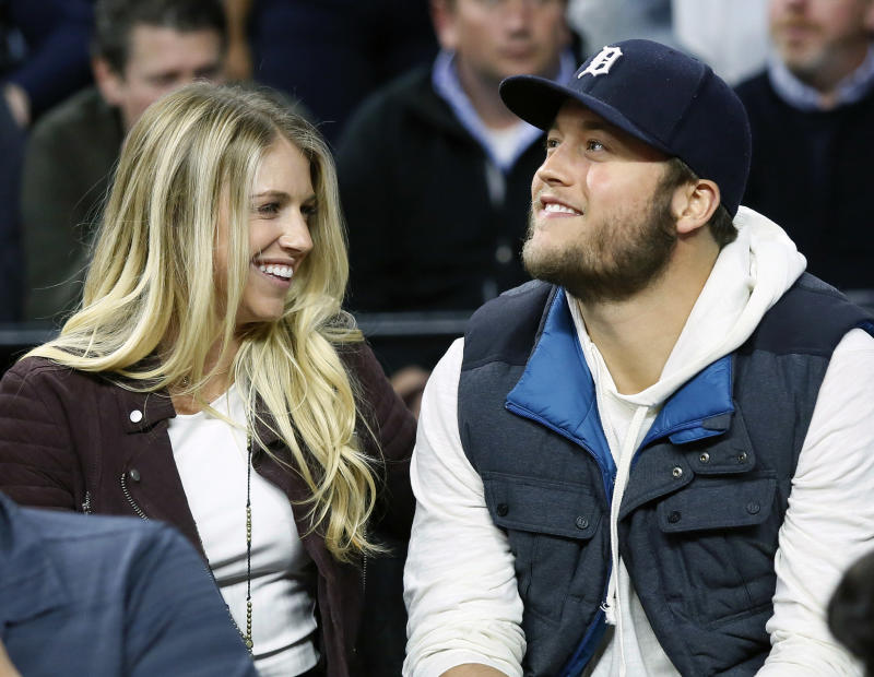 Detroit Lions quarterback Matthew Stafford, right, smiles while watches the Detroit Pistons play the Cleveland Cavaliers with his wife Kelly, left, during the first half of an NBA basketball game Tuesday, Nov. 17, 2015, in Auburn Hills, Mich. (AP Photo/Duane Burleson)
