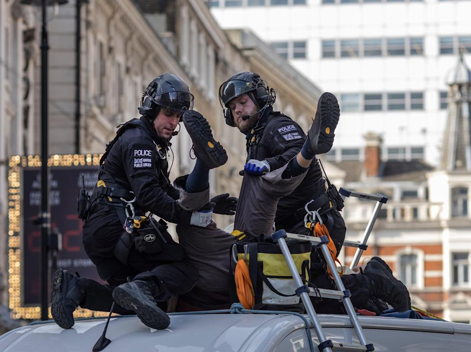 An XR protester, who installed himself on top of a van near Covent Garden, is arrested by police (Getty)
