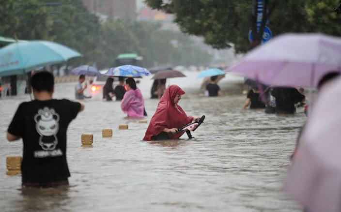 Residents wade through floodwaters on a flooded road during heavy rainfall in Zhengzhou, Henan province - CHINA DAILY