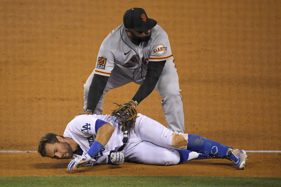San Francisco Giants third baseman Pablo Sandoval, top, checks on Los Angeles Dodgers' Chris Taylor after they collided while Taylor was running to first on a single during the fifth inning of a baseball game Friday, July 24, 2020, in Los Angeles. Taylor was able to continue. (AP Photo/Mark J. Terrill)