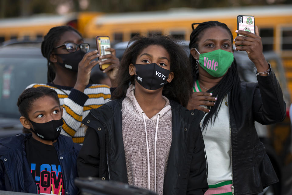 A family listens to Vice President-elect Kamala Harris speak at a drive-in rally during a campaign stop for Democratic U.S. Senate candidates the Rev. Raphael Warnock and Jon Ossoff, Sunday, Jan. 3, 2021, in Savannah, Ga. (AP Photo/Stephen B. Morton)